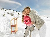 stock photo of toboggan  - Young Mother And Daughter On Winter Vacation - JPG