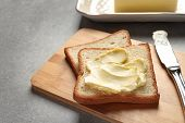 Tasty Bread With Butter And Knife On Wooden Board poster