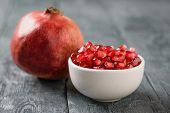 Ripe Pomegranate And Pomegranate Seeds In A White Bowl On A Black Wooden Table. Harvest Ripe Pomegra poster