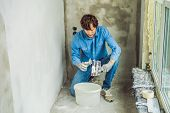Master Is Applying White Putty On A Wall And Smearing By Putty Knife In A Room Of Renovating House I poster
