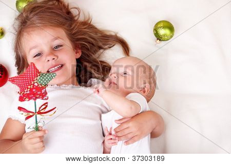 Elder sister and newborn baby playing with  Christmas star