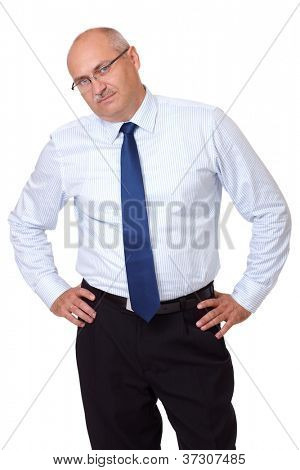 Portrait of bored senior businessman in blue shirt standing with hands on his hips, isolated on white