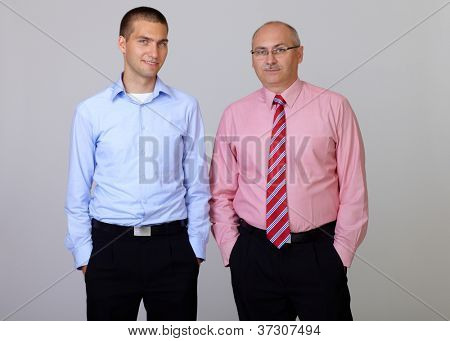 Happy smiling senior and junior businessman standing with hands in pockets, isolated on grey