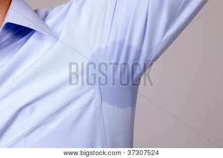 Man with hyperhidrosis sweating very badly under armpit in blue shirt, isolated on grey