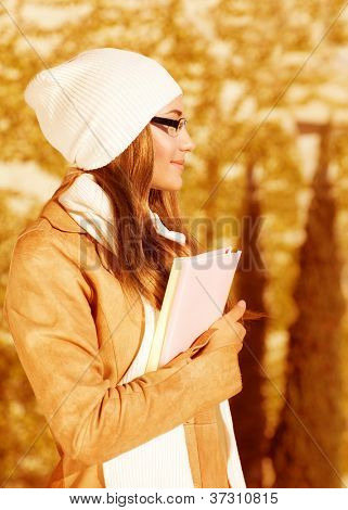 Photo of pretty student girl standing in autumn park and wearing beige leather coat with white warm hat, cute schoolgirl holding book, side view of beautiful teenager, back to school
