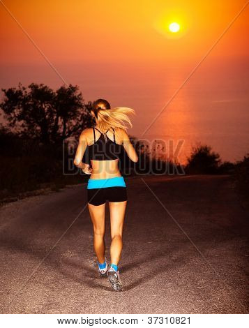 Picture of sporty blond female running along the road over sunset, beautiful active woman doing fitness exercise outdoors, rear view of healthy jogger girl wearing sports clothes, healthy lifestyle