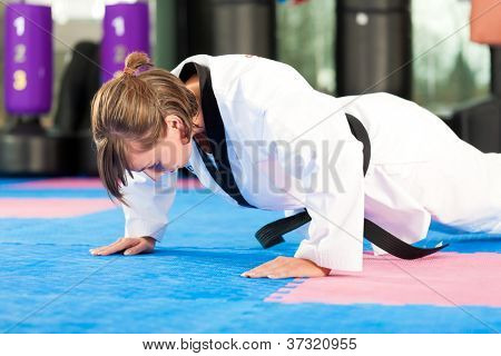 Woman in martial art training in a gym, she is stretching and warming up