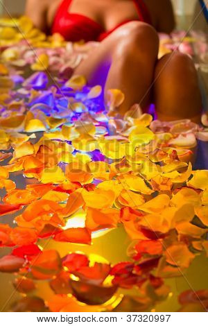 Woman bathing in spa with color therapy, the bathtub is lit with colorful lights, lots of flower petals on tub