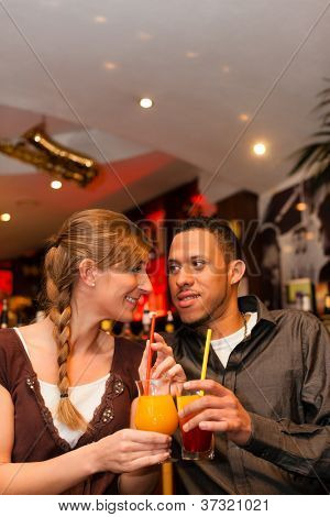 Young happy couple drinking cocktails in bar or restaurant, presumably it is a first date