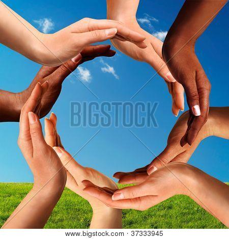 Paz conceitual e símbolo de diversidade cultural de multiracial mãos fazendo um círculo em azul