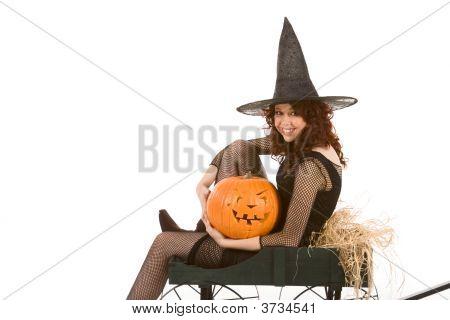 Teen Girl In Halloween Costume On Cart With Pumpkin