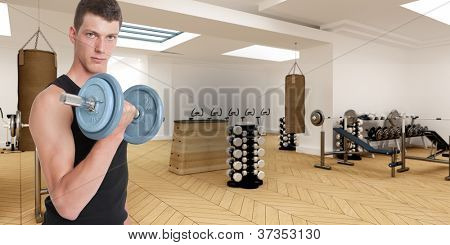 Young man in a gym lifting a dumbbell