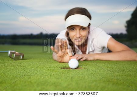 Smiling woman golf player lying on green and hitting the ball to drop into cup. Focus on ball and hole.
