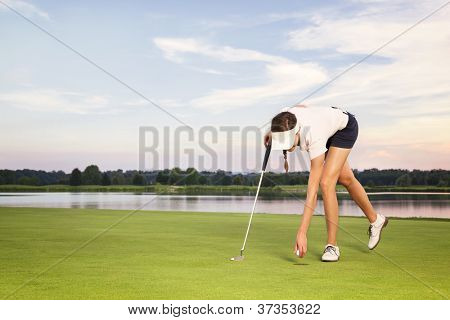 Woman golfer picking up golf ball from hole on green after putt.