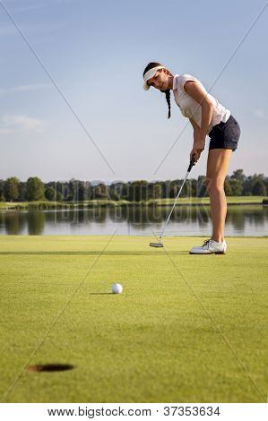 Woman golf player putting ball on green. Golf ball rolling towards cup.