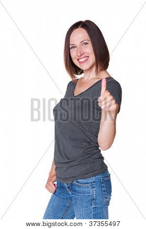 excited young woman in grey t-shirt and blue jeans showing thumbs up. studio shot over white background
