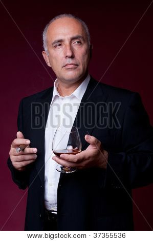 confident senior man with cigar and glass of cognac over dark red background