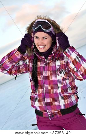 Smiling young woman wearing skiing suit posing outdoors in winter