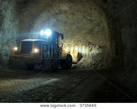 Bulldozer Loading Rocks In The Dark Of A Mine