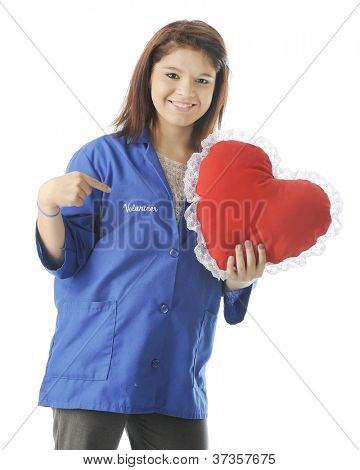 "A happy teen volunteer holding a heart-shaped pillow while pointing to the word ""volunteer"" on her volunteer smock.  On a white background."