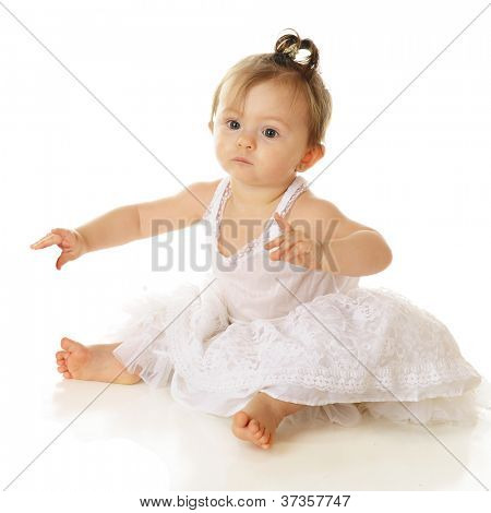 An adorable baby girl sitting pretty in her petticoat.  On a white background.