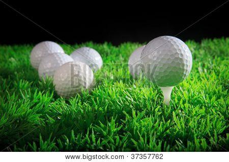 bola de golfe no tee branco com campo de grama verde