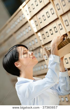 Woman looks for something in card catalog composed of set of wood boxes at the library. Education