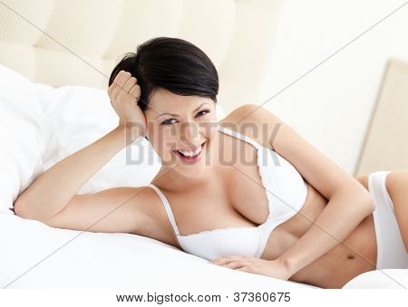 Woman in white bra is lying in the comfortable bed with white bedclothes