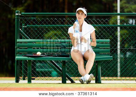 Tenista mujer descansa con botella de agua en el Banco en la cancha de tenis