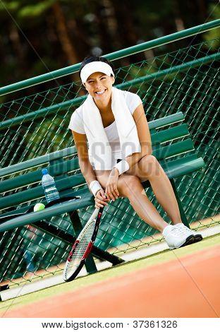 Joven tenista mujer descansa con botella de agua en el Banco en la cancha de tenis