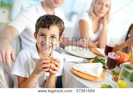 Portrait of happy boy with apple sitting at festive table and looking at camera with his family on background