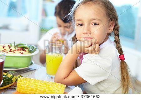 Porträt von glücklichen Mädchen sitzen an festlichen Tisch und Blick in die Kamera