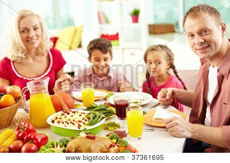 Portrait of happy family sitting at festive table and looking at camera while holding each other by hands
