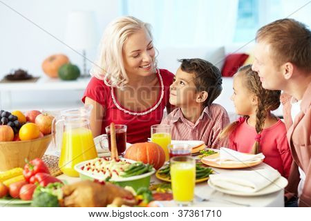 Portrait of happy family sitting at festive table and chatting