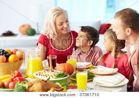 Portrait of happy Family an festlichen Tisch sitzen und im Chat