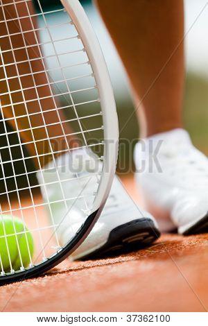 Legs of sportswoman near the tennis racket and balls