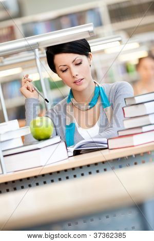 Woman with green apple surrounded with piles of books reads sitting at the table at the library. Studying process