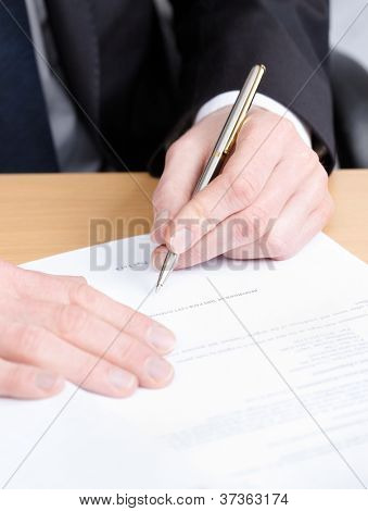 Sitting at the table business man making notes in the writing pad