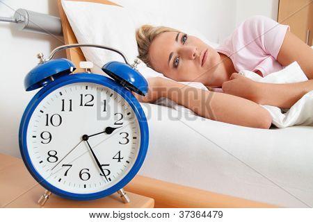 Slapeloosheid met klok in de nacht. vrouw kan niet slapen.