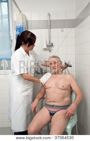a senior is bathed by nurses