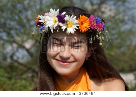 Cheerful Young Girl With A Wreath Of Flowers