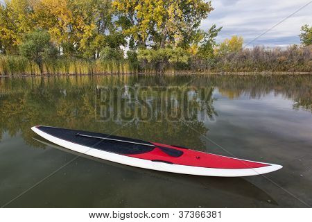 stand up paddleboard with paddle on a calm lake in fall scenery