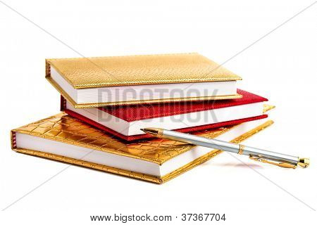 Golden and red notebooks with silver pen