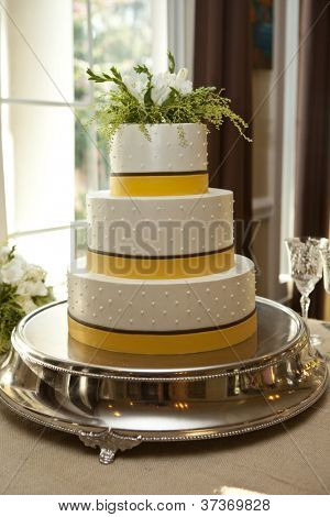 three tiered wedding cake in white, brown, and yellow.