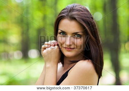 Gorgeous Woman Stading With Hands Near The Face In The Woods