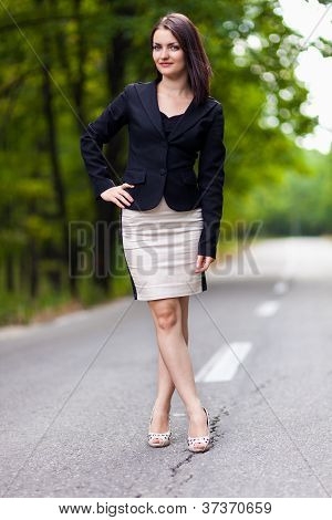 Young Businesswoman Standing On The Road With Hand On Hip And Cr