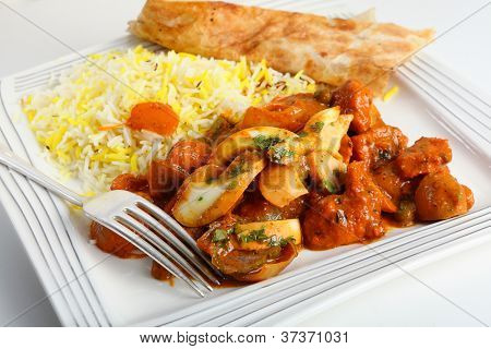 Chicken jalfrezi curry on a plate with pilau rice and a piece of naan bread.