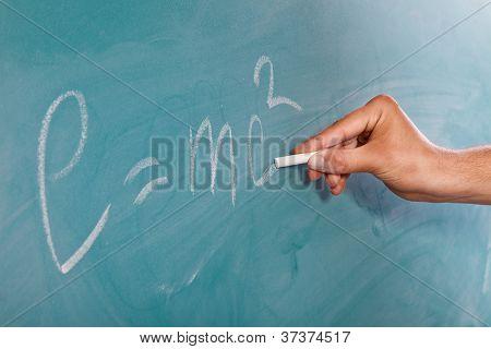 Einstein der Formel e = mc2 auf einer Tafel