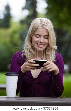 Feliz sonriente joven utilizando el teléfono móvil en el Parque