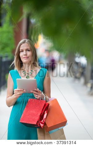 Portrait of a pretty young woman with shopping bags and digital tablet on sidewalk
